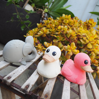Two kawan ducks toys and a grey whale toy on a wood chair