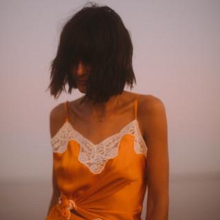Brunette woman wearing an orange top