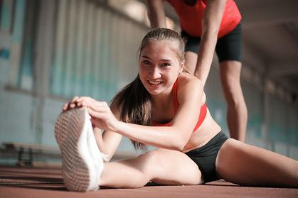 happy-sportswoman-stretching-legs-on-flo