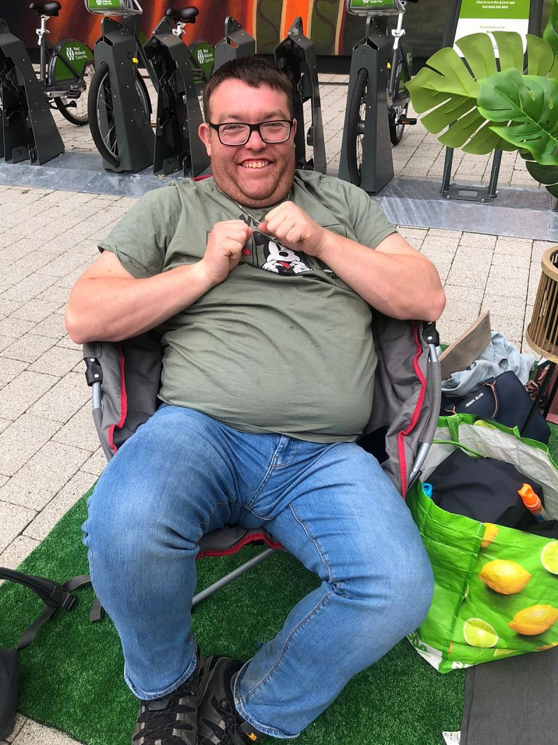 A man wearing a green t-shirt smiles as he sits in a camping chair at a Grapevine parklet in Coventry