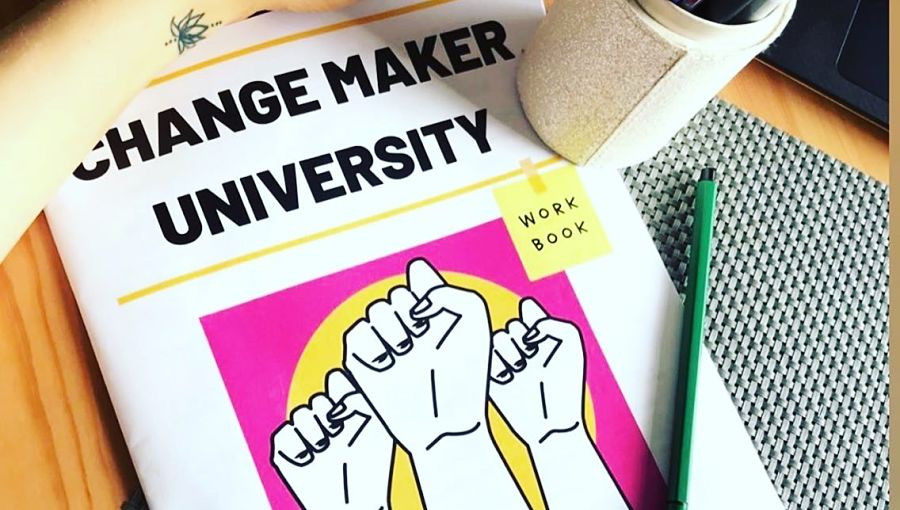 A Changemaker University workbook sits on a desk alongside a pen pot, pencil and someone's arm. The arm has a small tattoo near the wrist.