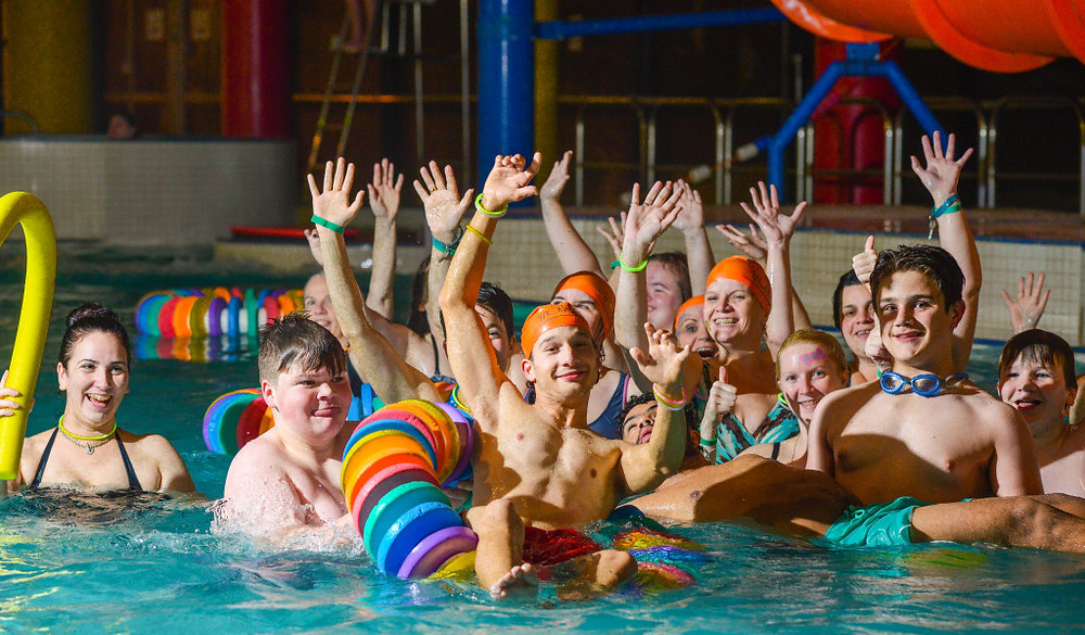 A group of people in an indoor swimming pool enjoying a wave rave.