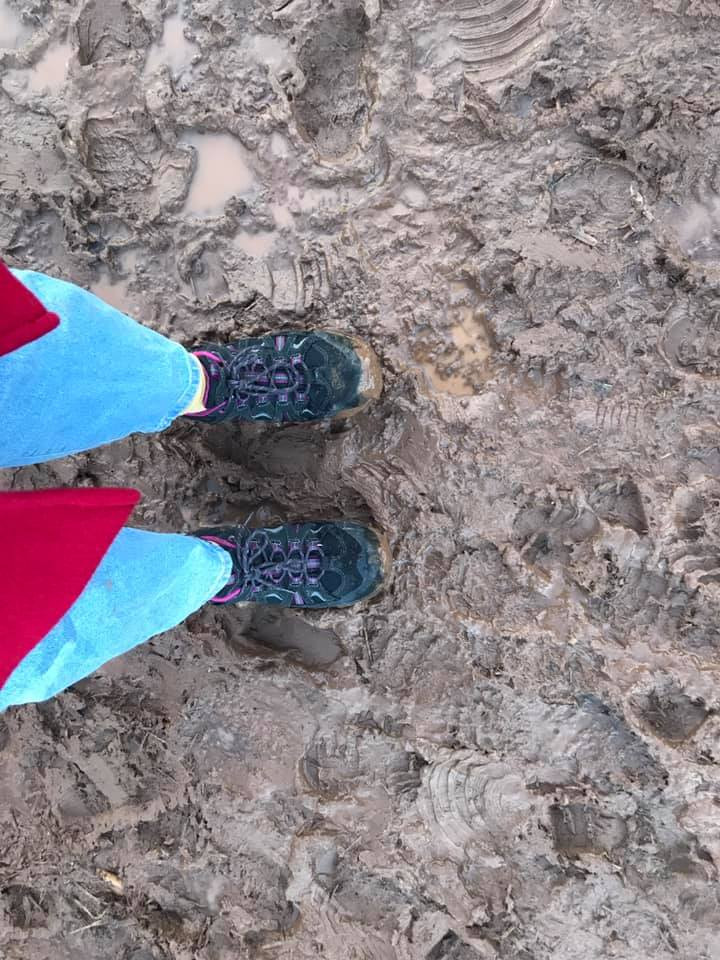 Image taken looking down on walking boots on mud.