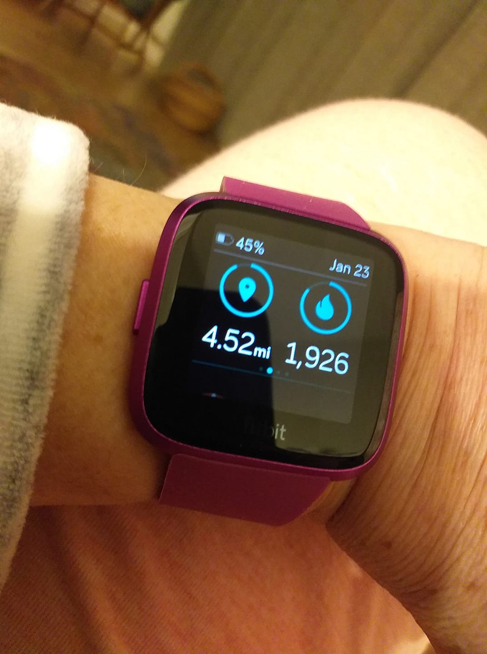 A fitness watch on someone's wrist displays distance and number of steps data.