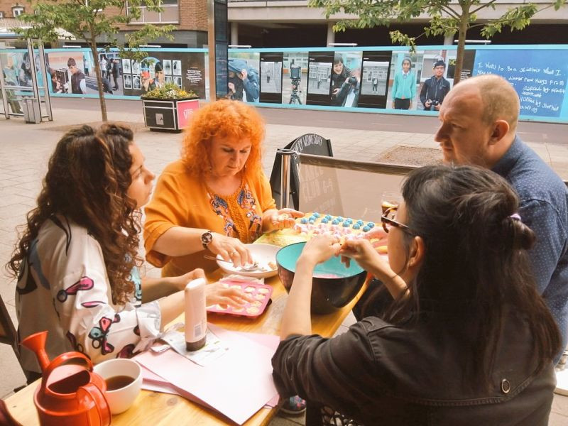 Four people, one man and three women, sit around a table outside a bar in Coventry making seed bombs. They are talking together.