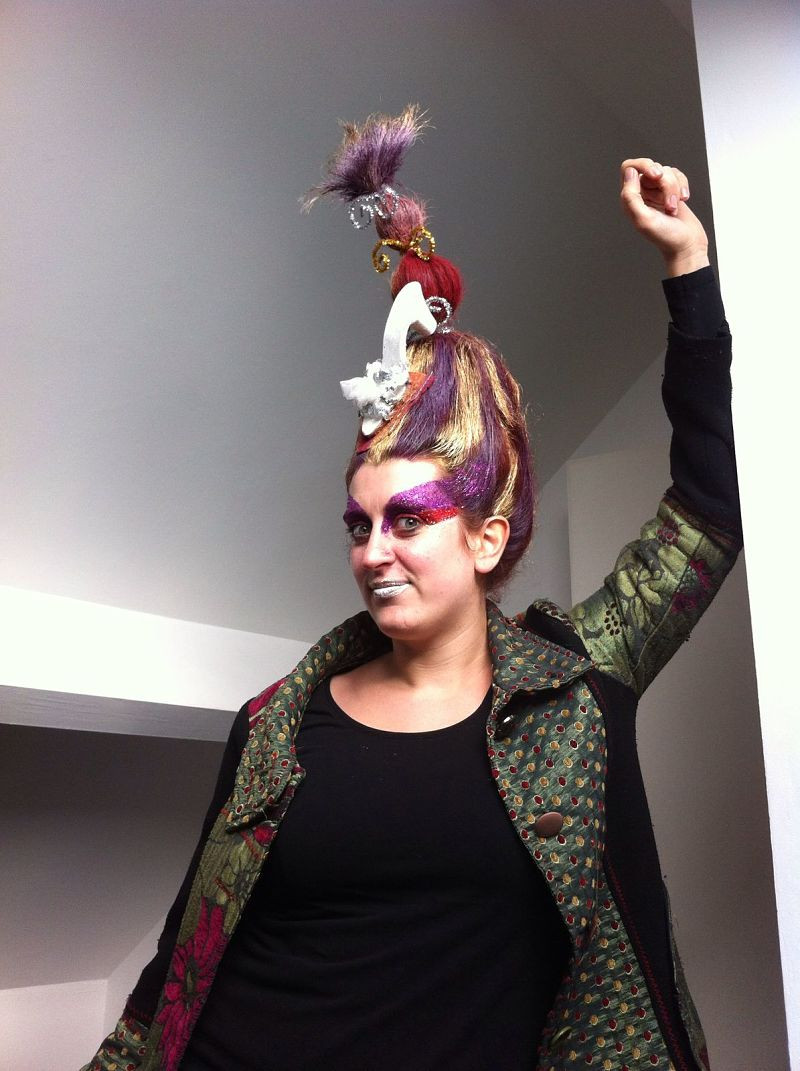 A woman leans against a wall wearing bright make up, colourful hair and a costume jacket