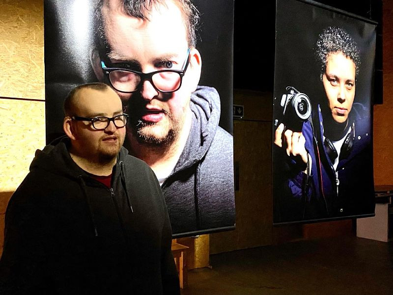 Aman wearing glasses and a black hoody stands in front of a large studio photograph of him. Another photo is alongside