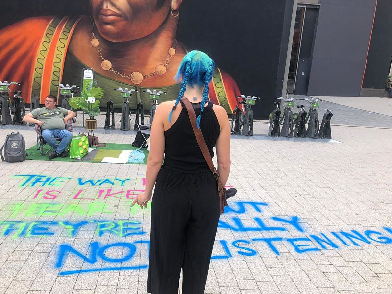 A woman with blue hair in pigtails read a quote sprayed on the floor at a parklet in Coventry