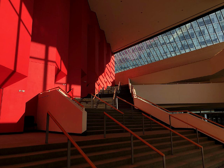Red multi-angular wall with linear shadows abuts an ascending staricase flanked by a long skylight o
