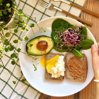 Pan de trigo sarraceno con tahin, huevo poché, aguacate, espinacas y germinados de rábanos