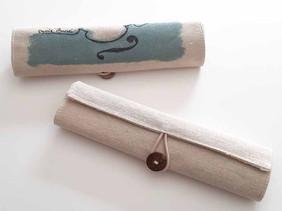 Fet de jute i cotó, amb una tanca elegant de botó. Conté 5 peces d'acabat nature: Goma d'esborrar, bolígraf de cartró reciclat, amb maquineta, llapis i regla de fusta. 20 x 20 x cm   70 gr.