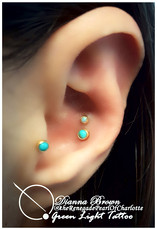 Double conch piercing and tragus piercing, all with synththetic turquoise set in yellow gold