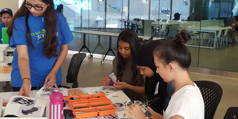 Three elementary school girls are learning robotics with a university student facilitator at a Let's Talk Science summer computer science camp at Ryerson University