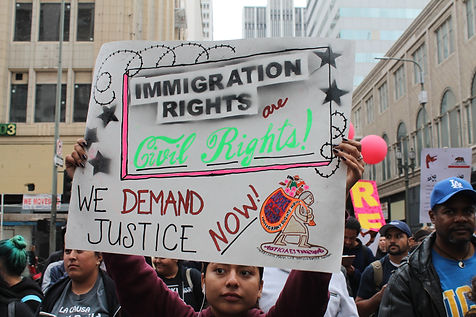 A young girl is holding a sign demanding justice for immigrants.