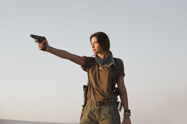 woman-standing-with-a-gun-outdoors-in-de