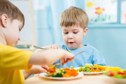 kids eating food in nursery or at home.j
