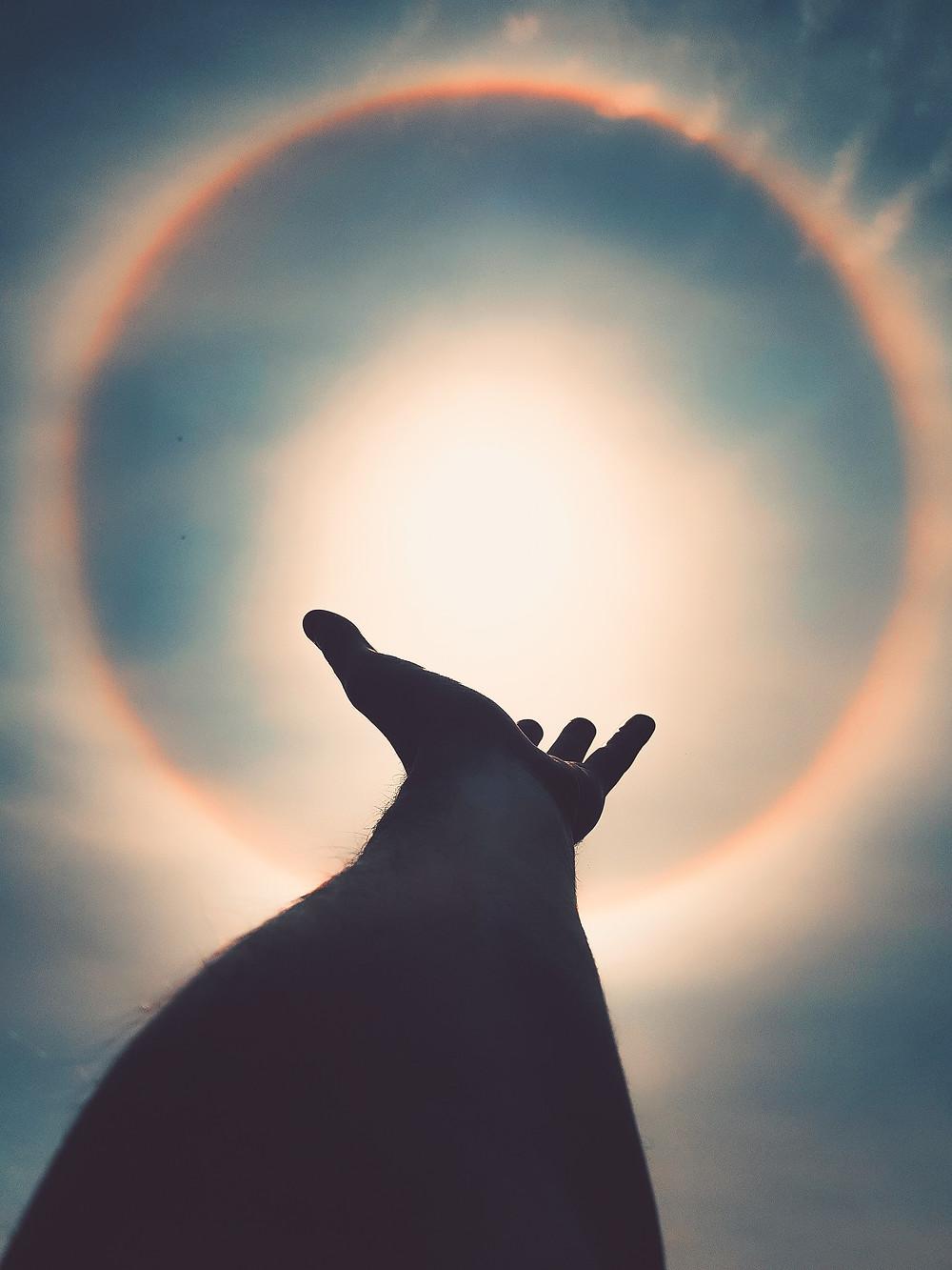 Hand extending towards sun
