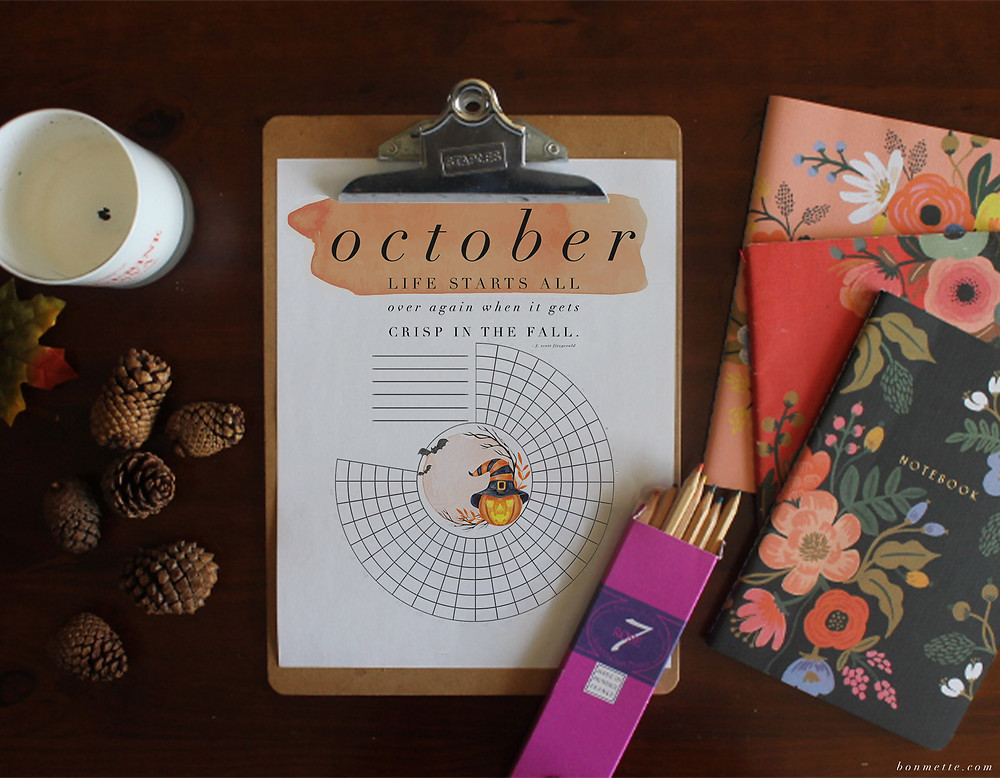An October free download habit tracker on a table with fall notebooks, colored pencils, and pinecones.