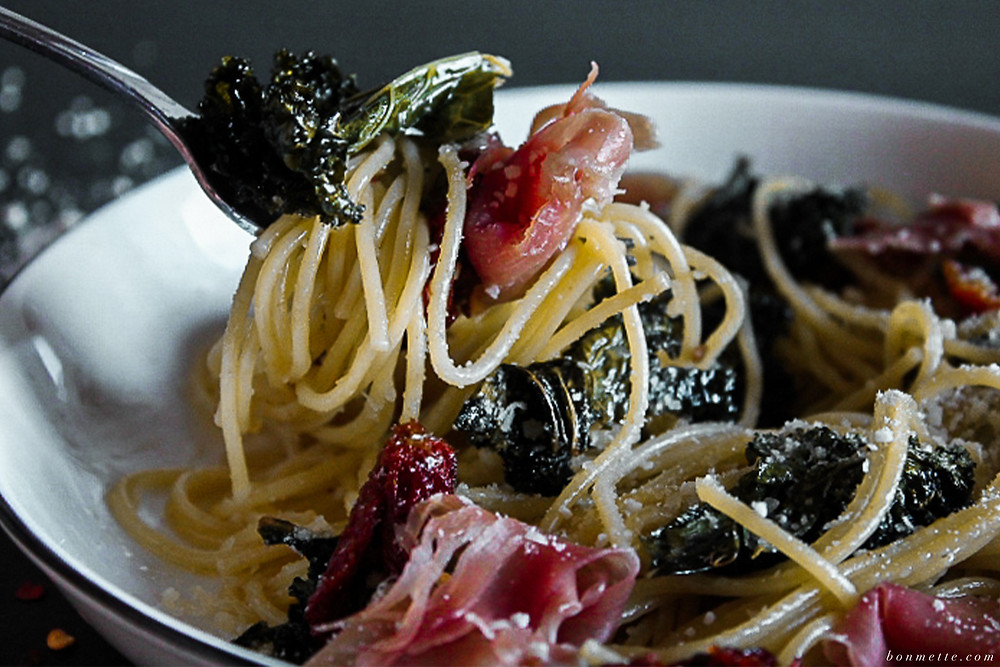 Fork holding spaghetti with kale, prosciutto, and sun-dried tomato