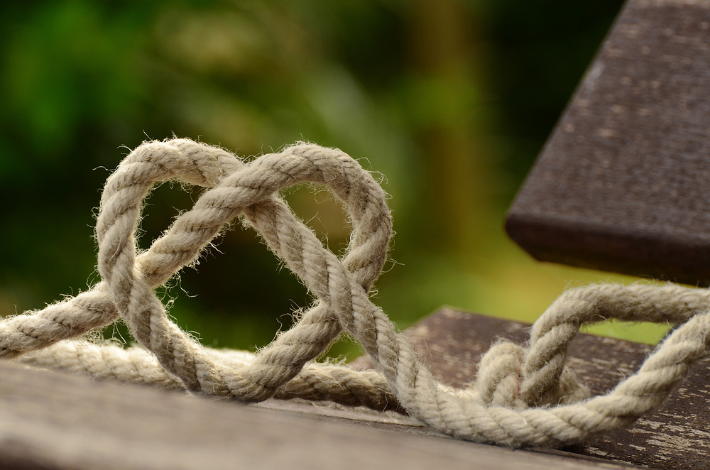 A heart shaped knot in a rope, against a wooden background illustrating the idea that knots in umbilical cords are not as dangerous as we have been led to believe