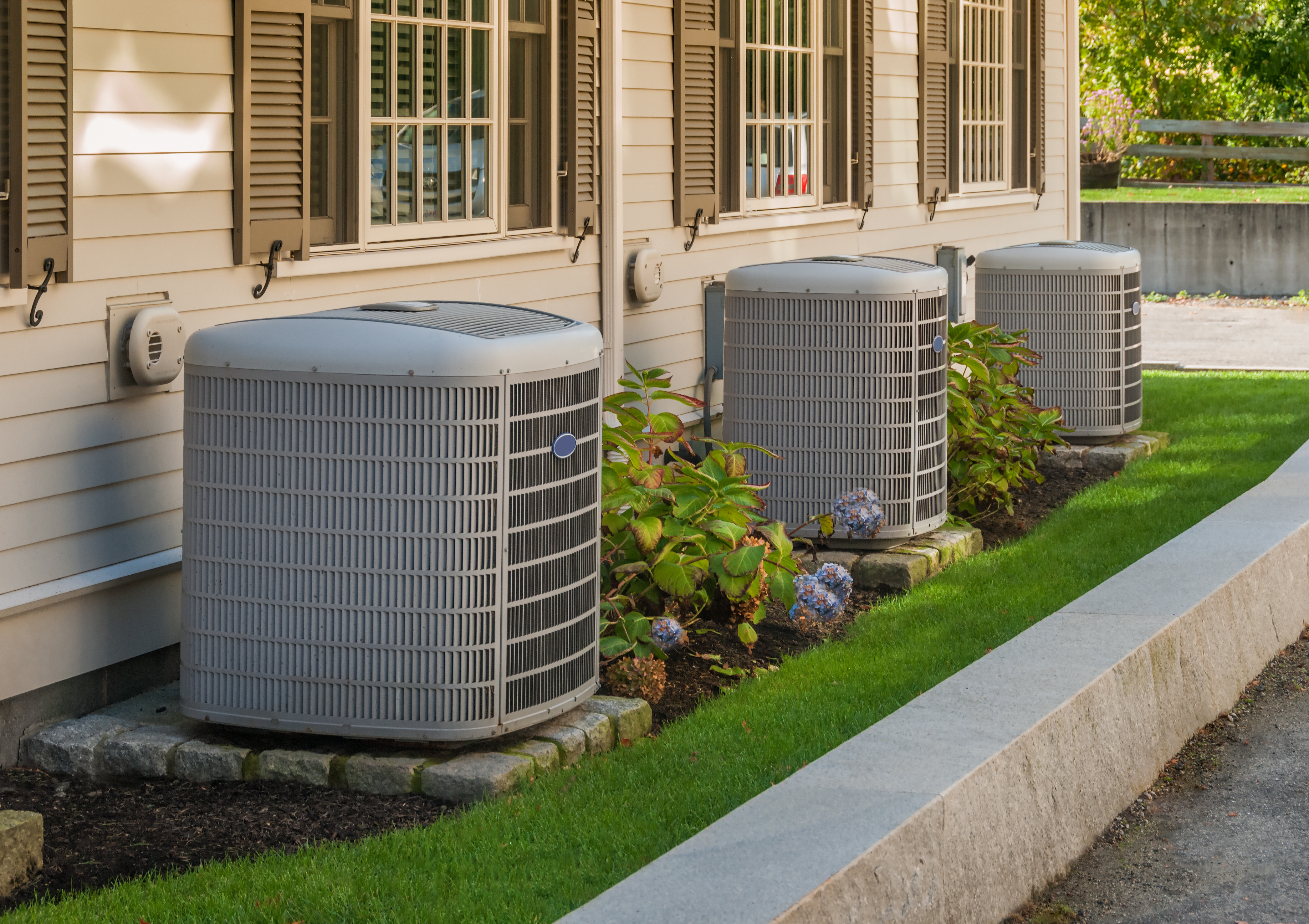 Heating and air conditioning inverters on the side of a condo_