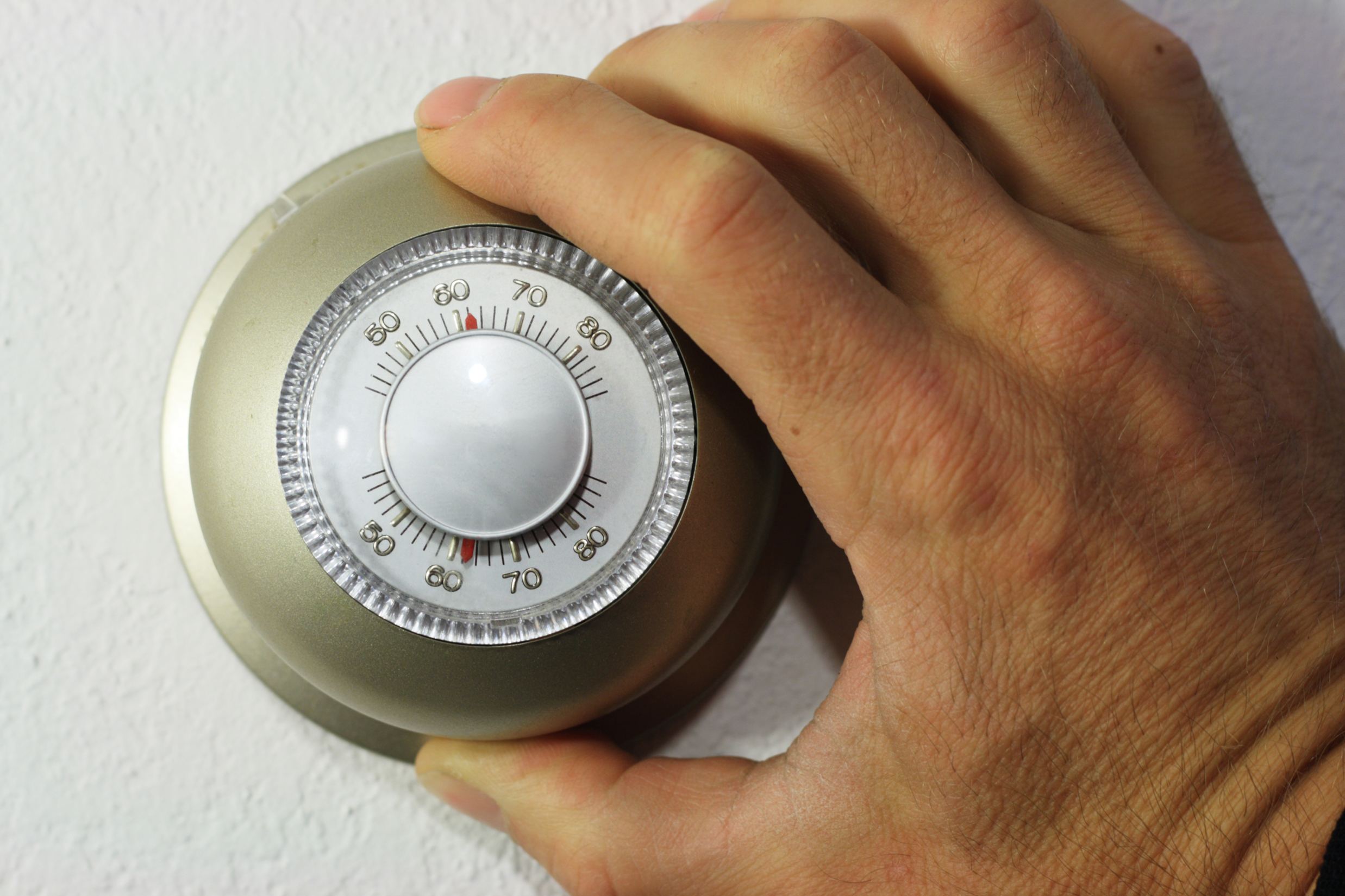 hand setting a thermostat down to 62 degrees