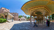 As described by several Western visitors (such as the Córdoban nobleman Pero Tafur[37] and the Florentine Cristoforo Buondelmonti),[38] the church was in a dilapidated state, with several of its doors fallen from their hinges; Mehmed II ordered a renovation as well as the conversion. Mehmet attended the first Friday prayer in the mosque on 1 June 1453.[39] Aya Sofya became the first imperial mosque of Istanbul.[40] To the corresponding Waqf were endowed most of the existing houses in the city and the area of the future Topkapı Palace.[29] From 1478, 2,360 shops, 1,300 houses, 4 caravanserais, 30 boza shops, and 23 shops of sheep heads and trotters gave their income to the foundation.[41] Through the imperial charters of 1520 (AH 926) and 1547 (AH 954) shops and parts of the Grand Bazaar and other markets were added to the foundation.[29]   The mihrab located in the apse where the altar used to stand, pointing towards Mecca Before 1481, a small minaret was erected on the southwest corner of the building, above the stair tower.[29] Later, the subsequent sultan, Bayezid II (1481–1512), built another minaret at the northeast corner.[29] One of these collapsed after the earthquake of