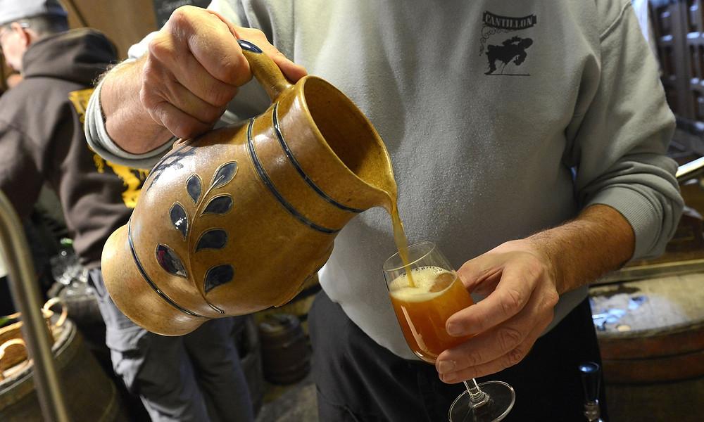 A produção de Cervejas do tipo Lambic está ameaçada devido as mudanças climáticas. Na foto, homem serve uma Lambic em taça.