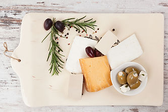 Charcuterie with Cheese, Olives, Herbs on a Cutting Board