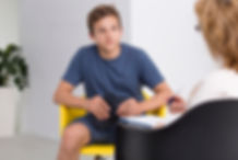 Teenager sitting in a chair at a therapy session.