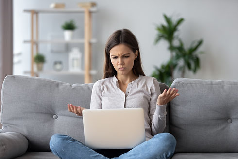 Confused young woman looking on laptop a