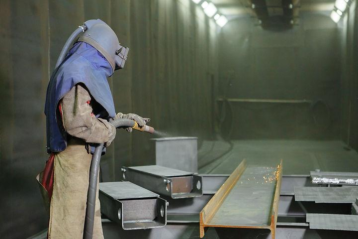 Sandblast. An employee prepares a metal