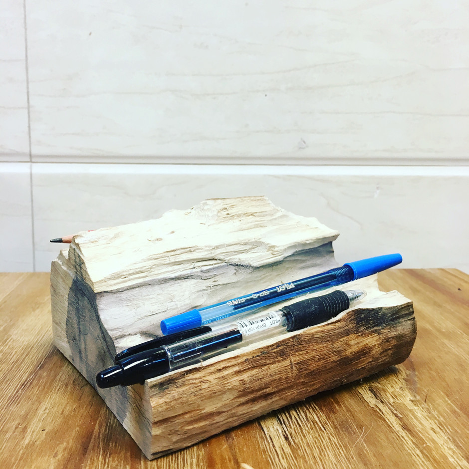 She carving recycled wood for pen storage~