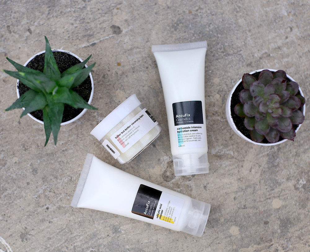 Photograph of products by AccuFix Cosmetics. Three products are shown alongside small, indoor potted plants. AccuFix Butter but Better Cleansing Balm, AccuFix Carbamide Intensive Hydration Cream and AccuFix Salicylic Acid Cleanser