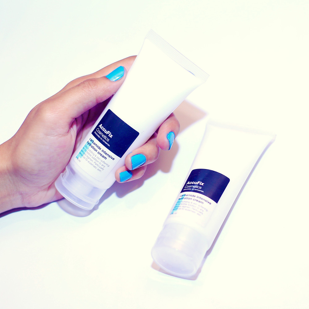 The AccuFix Carbamide Intensive Hydration Cream held in a hand wearing beautiful blue nail polish