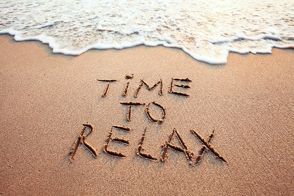 time to relax concept written on sandy b