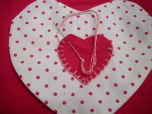 Blanket stitching little heart to big heart.