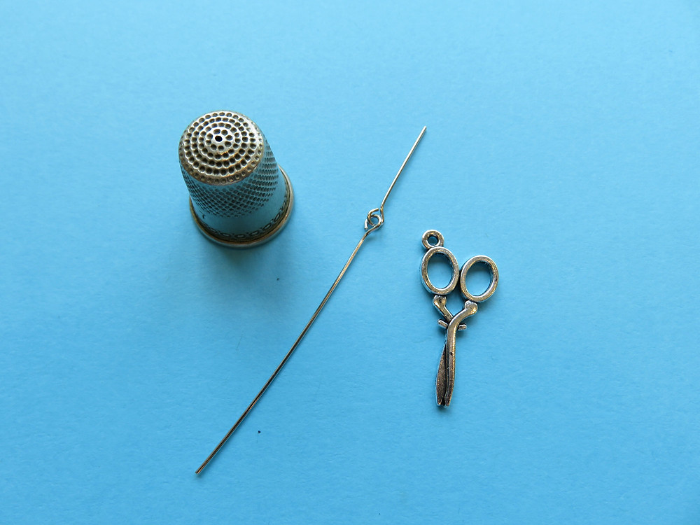 Thimble, eye pins and charm