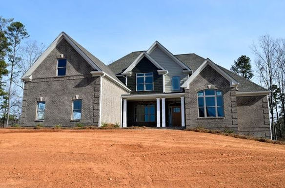 New home construction with gray brick exterior and keystone accents