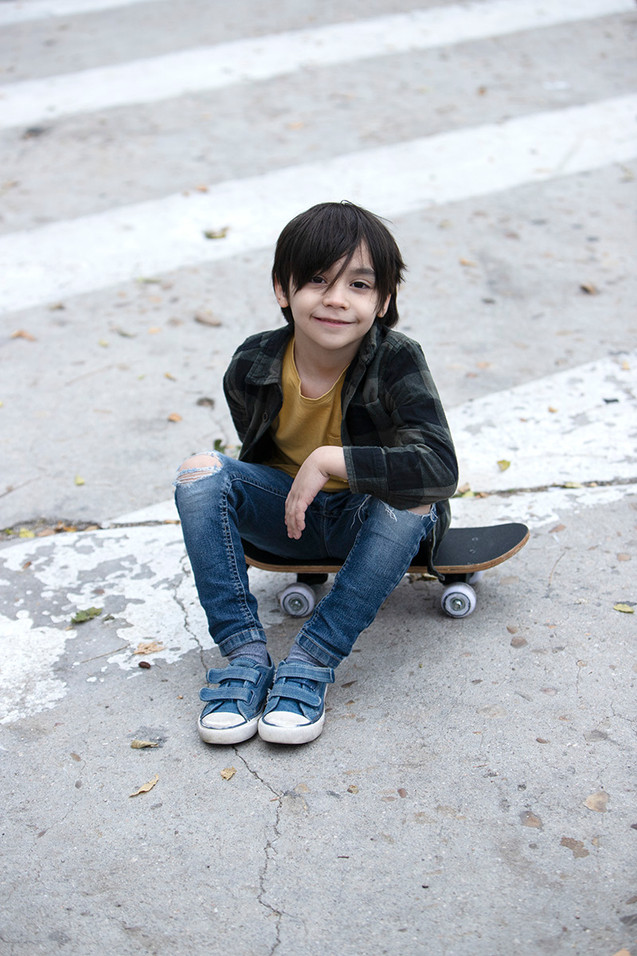 Cool kid sitting on his skateboard in th