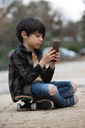 child outdoors playing with his mobile p