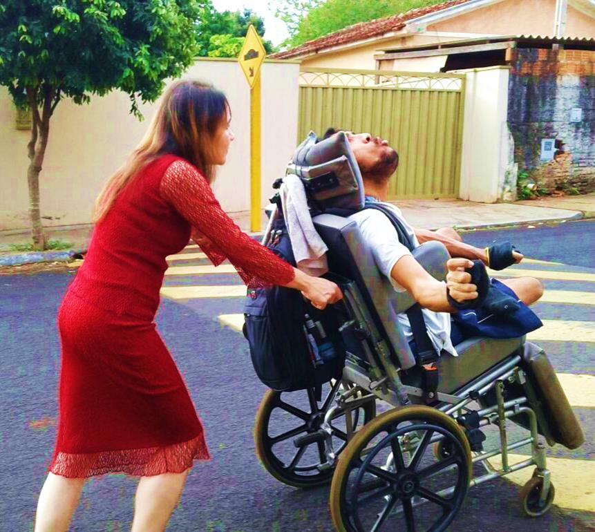 mulher de vestido longo e vermelho empurra o filho cadeirante, com espasticidade pelo esperado contato com o vento