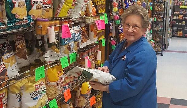Cash Market Associate holding bags of chip