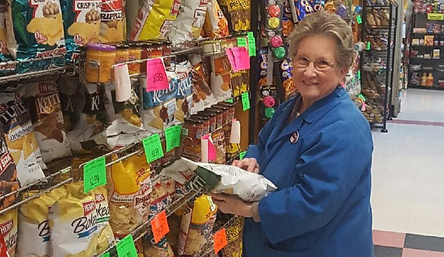 Cash Market Associate holding bags of chip