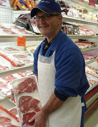 Cash Market butcher showing selection of meat in the meat department