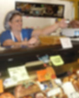 Smiling Cash Market associate serving a customer at the Cheese and Charcuterie Department