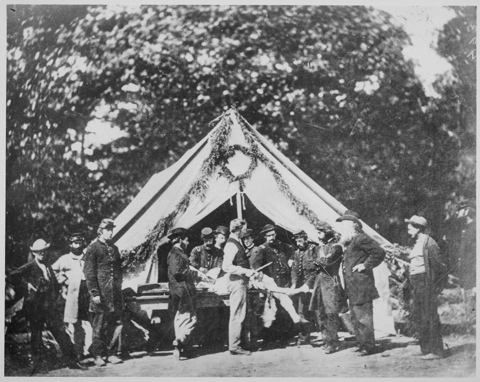 An amputation being performed in a field hospital in Gettysburg, PA. Note the evergreen boughs hung above the tent as an air freshener.