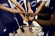Team Putting Fists Together In Huddle