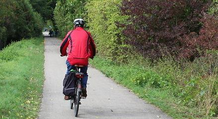 Mann mit Fahrrad auf Radweg