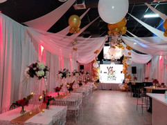 Banquet hall with red lights and white fabric hanging from the ceiling